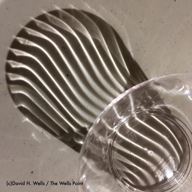 The play of light and shadow from a plastic cuphellip